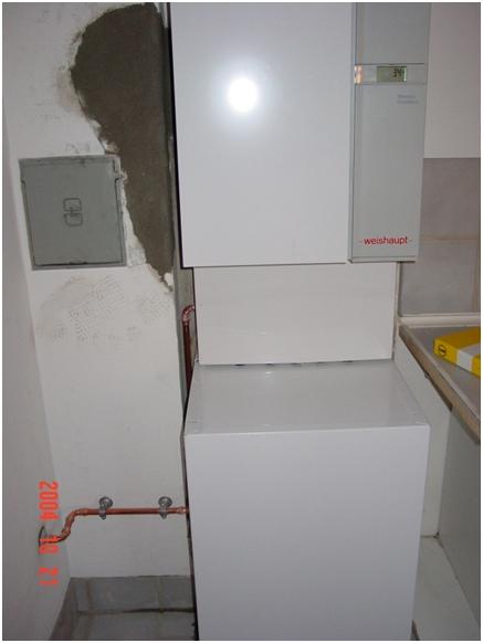 Figur 6 installation er færdig afdækning mellem kedel og varmtvandsbeholder er monteret, gas er ført ind til venstre for vvb, hul i skorsten er muret op